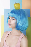 Imagination. Asian Woman in Blue Wig with Apple on her Head