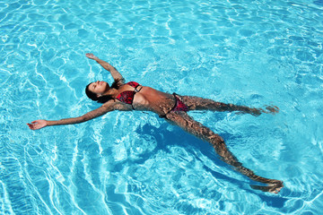 Young woman relaxing in pool.