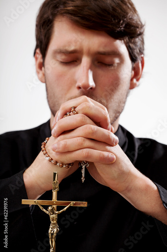 Priest is praying the rosary