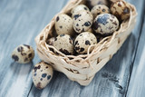 Wicker basket with raw quail eggs, horizontal shot