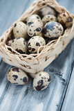 Wicker basket with quail eggs over wooden background