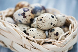 Close-up of raw quail eggs in a wicker basket