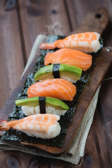 Sushi set on a rustic wooden cutting board, vertical shot