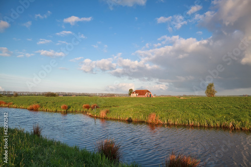 cozy farmhouse by river during sunny summer morning