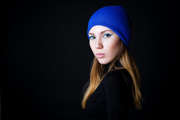 Fashion model with creative blue make up in blue hat