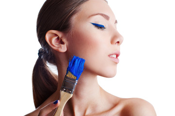 Fashion model with creative make up holding blue paintbrush
