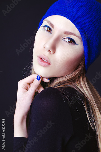 Fashion model with creative blue make up and blue nails in blue