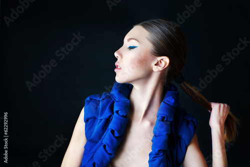 Fashion model with stylish blue make up holding her tail
