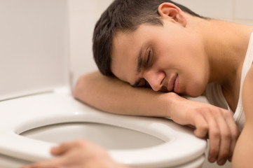 young man lying on toilet seat.