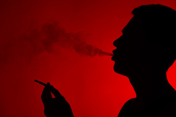 young man smoking cigarette on red.