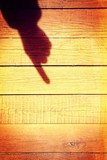 Shadow of a hand with a pointing finger on the wooden background