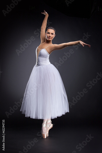 beautiful young ballet dancer on black.
