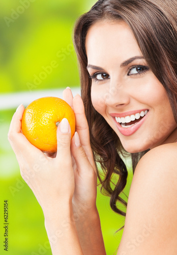 canvas print picture Young woman with orange, outdoors
