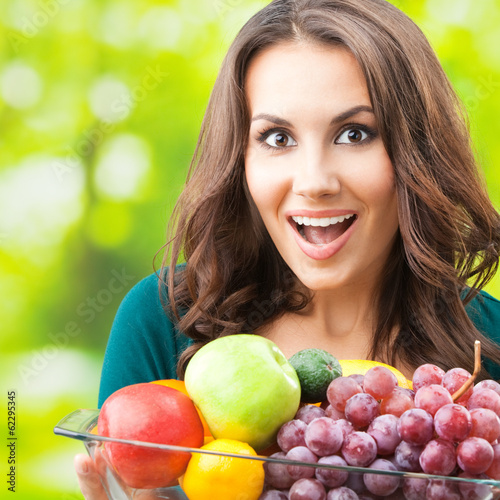 Woman with plate of fruits, outdoors