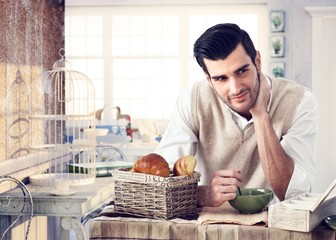 Handsome man having breakfast in cottage interior