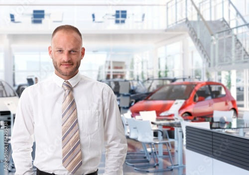 Portrait of car salesman in showroom