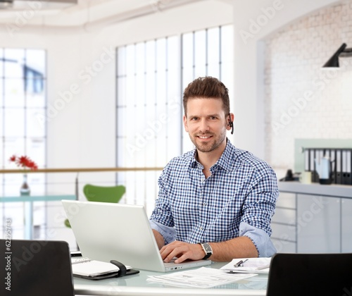 Entrepreneur working with laptop at office desk