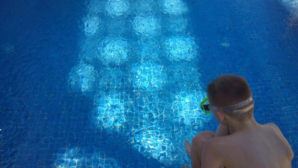 The young diver in front of the blue swimming pool