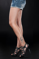 beautiful girl legs with tattoo symbol.