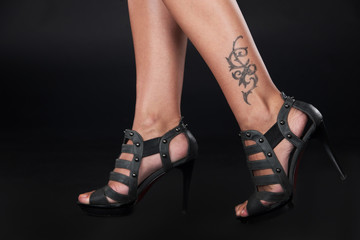 pretty lady tattooed legs on black.