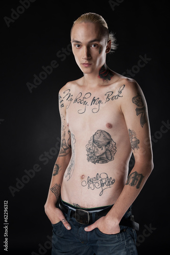 nude young man with tattoo on chest.