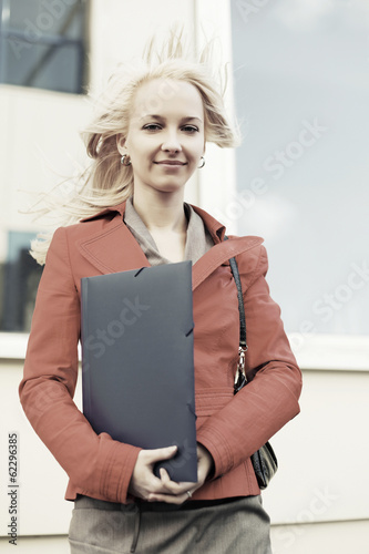 Happy young businesswoman with a folder