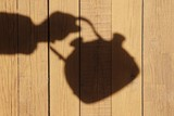 Silhouette with Kettle on the Natural Wooden Panel
