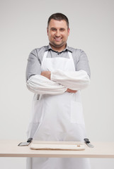 smiling butcher standing behind table.