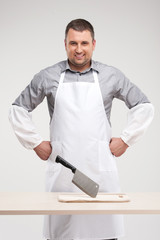 professional butcher smiling behind table.