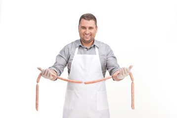 professional cook holding sausage and smiling.