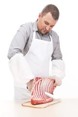 professional butcher cutting ribs on board.