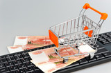 Shopping cart with money on black keyboard on gray