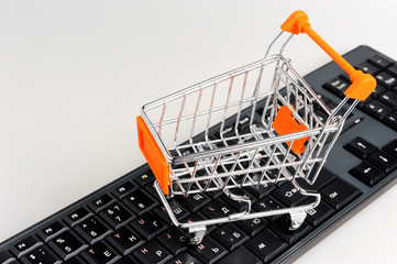 Shopping cart on black keyboard on gray