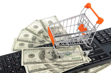Shopping cart with money on black keyboard isolated on white