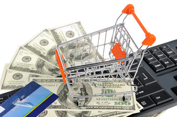 Shopping cart with money and credit card on black keyboard isola
