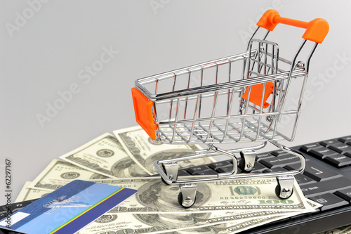 Shopping cart with money, credit card on black keyboard on gray
