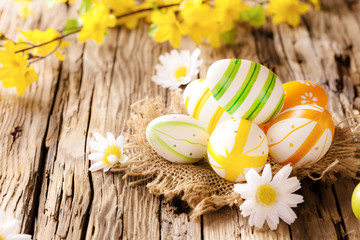 Easter eggs in nest on wooden surface