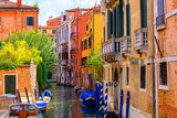 multicolored houses astride one of Venetian canals.