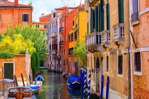 City on the water multicolored houses astride one of Venetian canals.