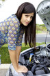 Sad woman in front of broken car