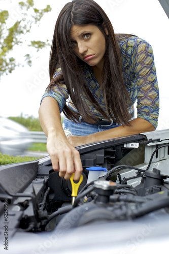 Young woman trying to fix engine of broken car
