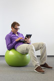 young man on stability ball  with tablet,relaxed position