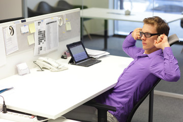 man exercising during work with tablet in his office