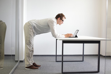 standing man typing at tablet in office, proper posture