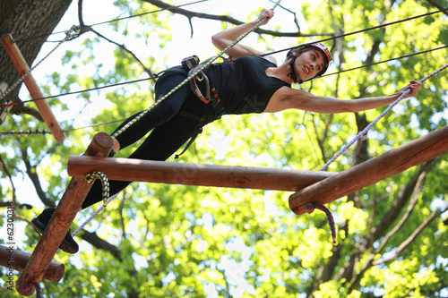 atractive woman climbing in adventure rope park