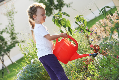 child with watering can at gardening