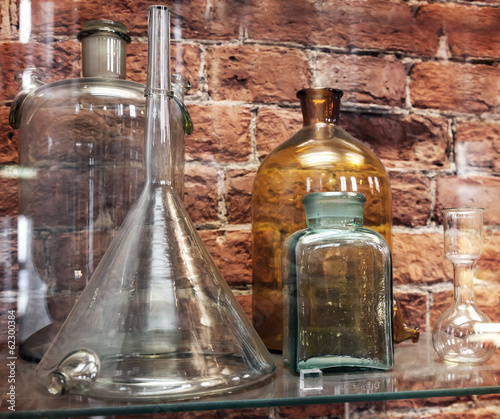 Vintage chemical ware is on the shelf on brick wall background