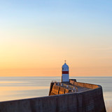 Lighthouse on breakwater wall with calm sea during sunrise