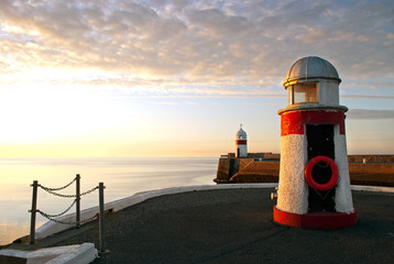 Lighthouses on breakwater wall with calm sea during sunrise
