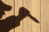 Silhouette with knife on the Natural Wooden Panel